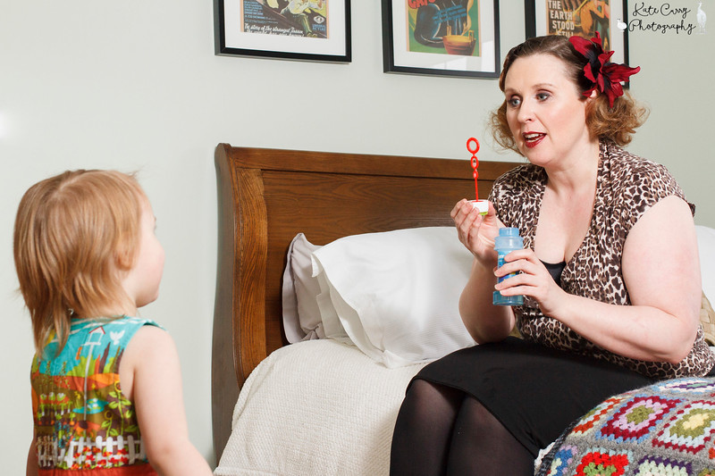 Vintage styled mum blowing bubbles for her young daughter, Lenzie