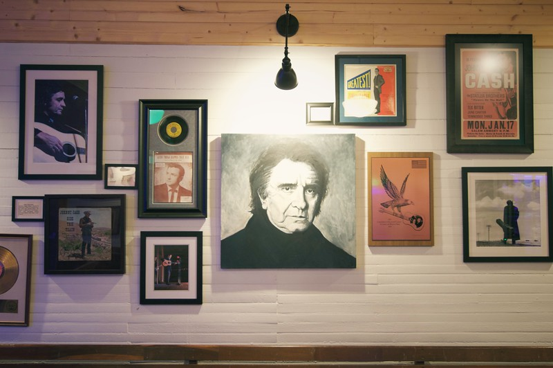A wall of framed photos include pictures of Johnny Cash