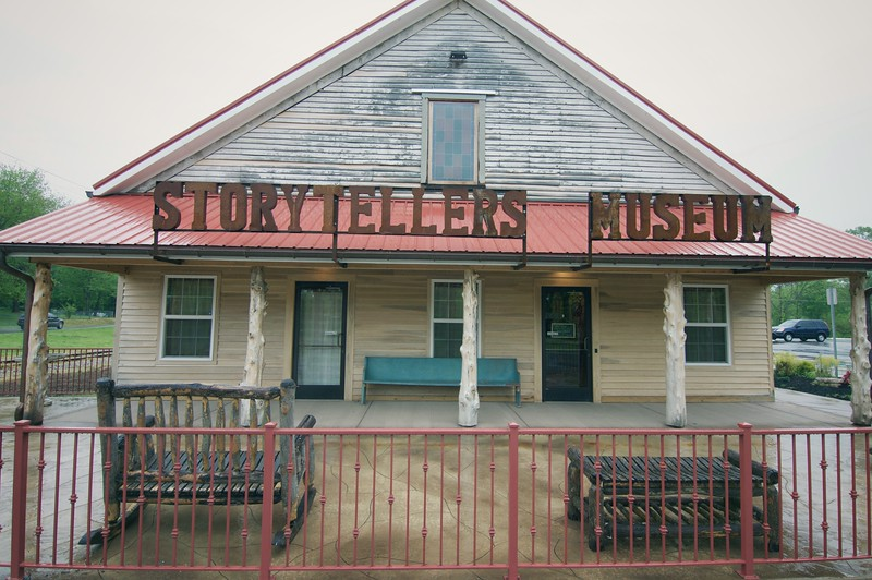 A wooden framed building has the letters saying Storytellers Museum