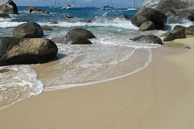 Waves, rocks and sand with a sea view.
