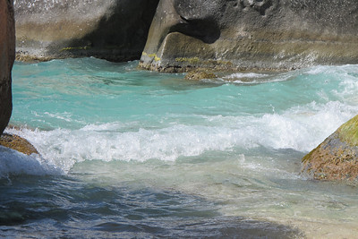 A small wave breaking amongst the rocks.