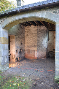 The brick construction is a hen house. Originally there was a cast iron cauldron in the corner which was heated with a coal fire which fed into the chimney to cook food, mainly potatoes, for the chickens and pigs.