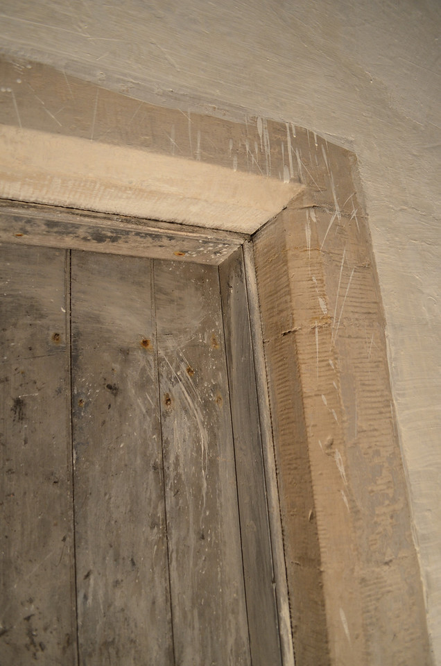 The doors are framed with these sandstone reveals. The rest of the building is constructed from very hard but inexpensive flint stone. The illusion once the flint stone had been plastered over was that the whole building would have been constructed from sandstone.