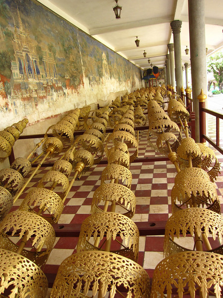 """Processional parasols stored in the gallery surrounding the Silver Pagoda. The crumbling mural on the wall depicts the <a href=""""http://en.wikipedia.org/wiki/Ramayana"""">Ramayana</a>."""