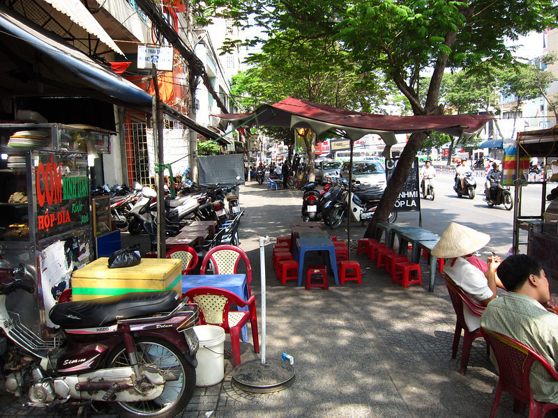 Typical Saigon street, with small tables and stools set up for a sidewalk restaurant.