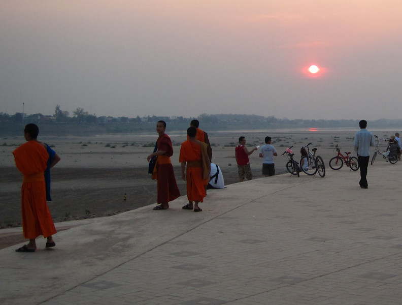 Monks at sunset on the Mekong