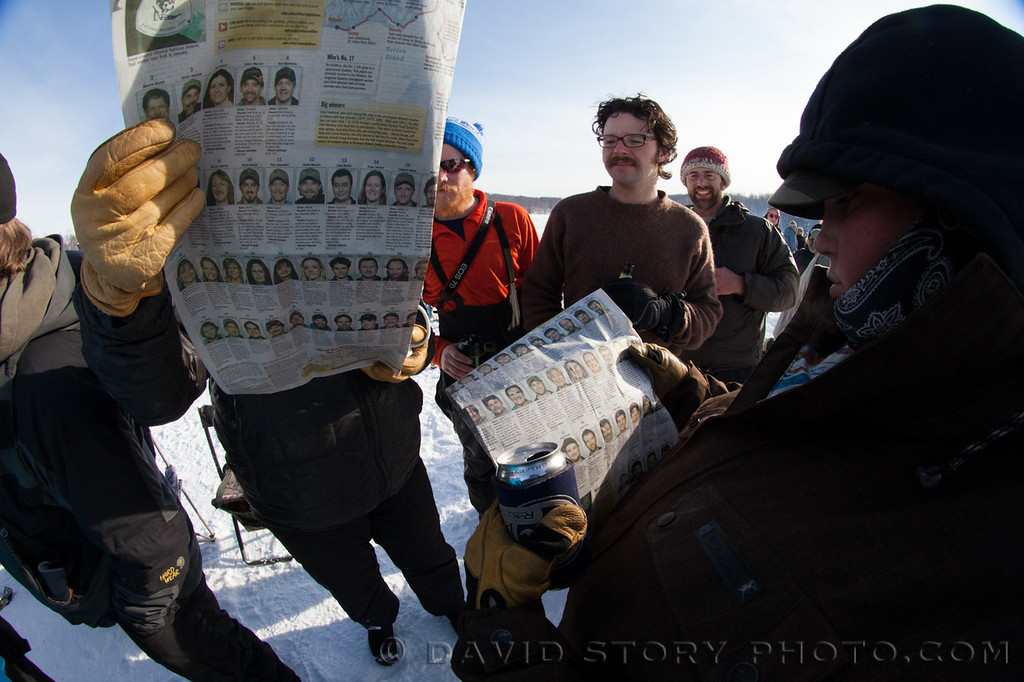 Spectators look over the list of mushers to see who will be approaching next at the 2013 Iditarod.