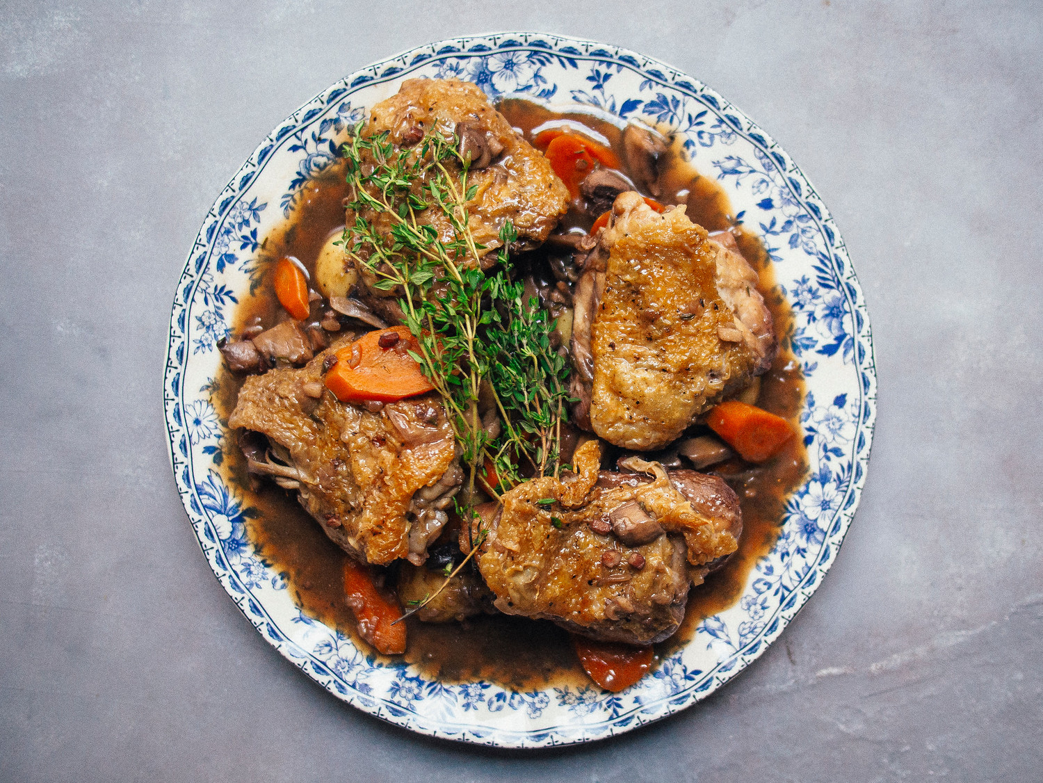 Instant pot coq au vin on a decorative blue plate on a grey background.