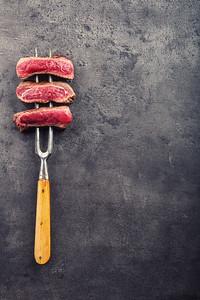 Steak. Grill beef steak. Slices of sirloin beef steak on meat fork on concrete background.