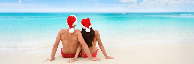 Christmas tropical sun vacation destination vacation holidays santa hat couple relaxing sitting on b