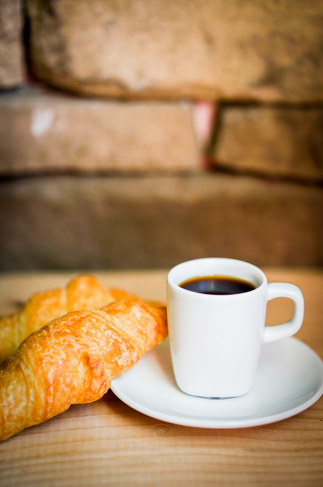 Black croissants with black coffee on wooden background