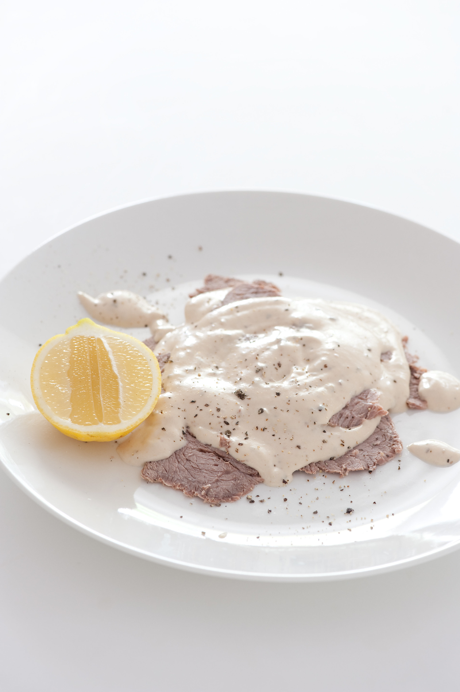 Vitello tonnato is veal in a tuna sauce on a white plate with lemon, a typical Milanese food.
