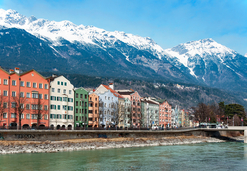 INNSBRUCK AUSTRIA - MARCH 3, 2010: Inn river historic houses and Alps covered with snow in Innsbruck Tirol Austria