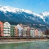 INNSBRUCK AUSTRIA - MARCH 3, 2010: Inn river historic houses and Alps covered with snow in Innsbruck Tirol Austria