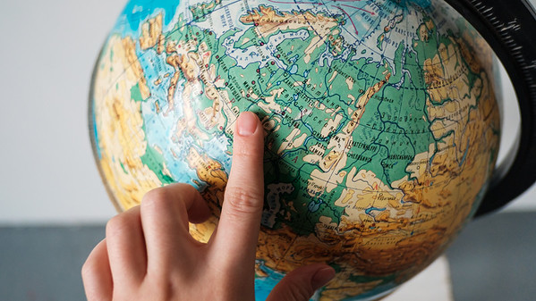 The girl points to a location on the world globe. Chooses a place to travel on the globe