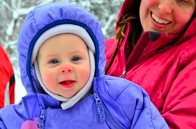 A mom holds her baby girl while they watch the Iditarod mushers pass by.