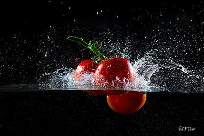 Three tomatos making a splash