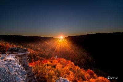Sun beams peaking over the mountain