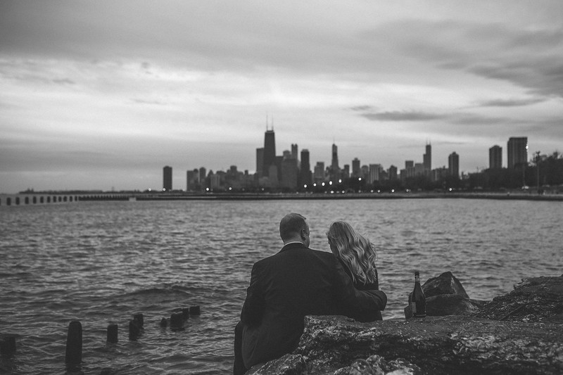 Katie and Dan's engagement session on the shoreline behind Lincoln Park where they shared in a champagne toast together during a romantic sunset with the Chicago skyline and lake behind them.
