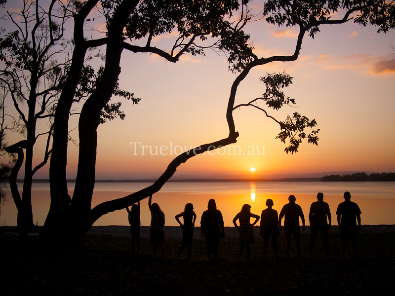 """20.1.2013<br /> <br /> A family at Sunset. I'm on holiday! Of course that doesn't mean leaving cameras at home. I saw this family by the water and saw a shot so I asked them to line up in height order under the tree. This seems to be my most popular shot on Flickr where I also post different works.<br /> <a href=""""http://www.flickr.com/photos/flowers71/"""">http://www.flickr.com/photos/flowers71/</a><br /> <br /> <br /> <br /> © Tess Peni"""