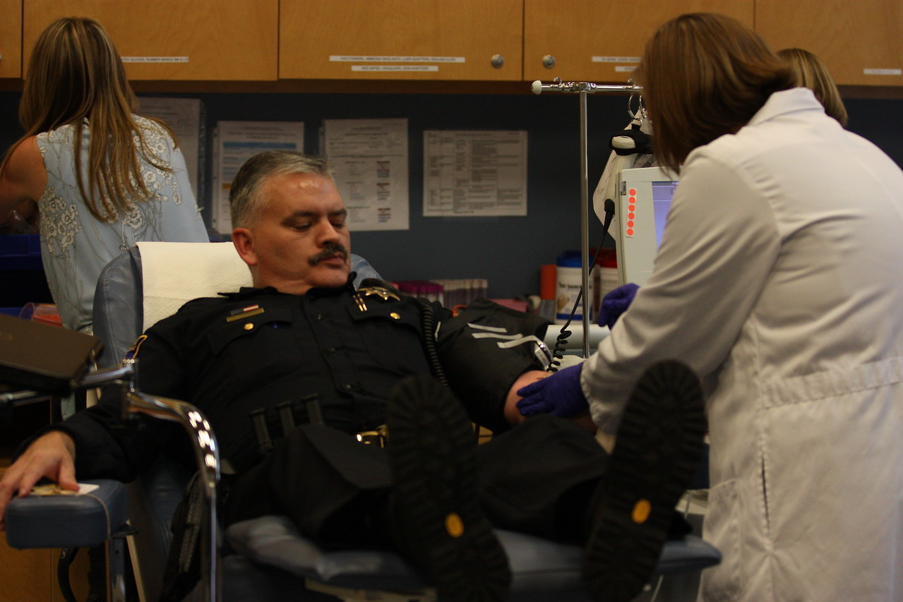 Eureka Police Capt. Brian Stephens makes a face as Northern California Community Blood Bank Director of Donor Services Tiffany Armstrong places a needle in his arm on Wednesday afternoon. (Will Houston - The Times-Standard)