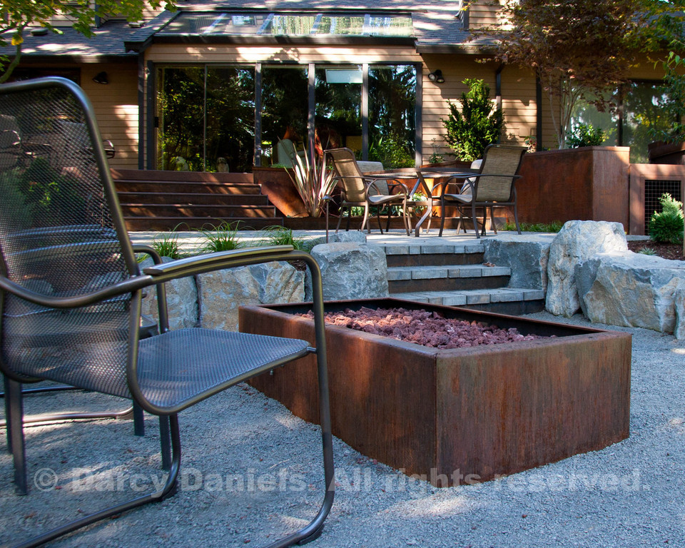 Steel and Stone: Gas fire pit fabricated in steel in foreground. Basalt boulders retain the grade.  Steel kick plates on steps. Raised beds buit into the deck are cor-ten steel. Garden Design: Darcy Daniels, Bloomtown Gardens. Landscape Contractor: Tryon Creek Landscape.