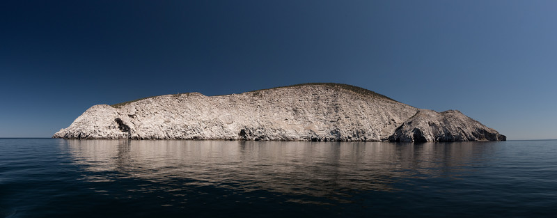 A panoramic view of Isla San Pedro Martir, showing the steep rocky cliffs that characterize its coast