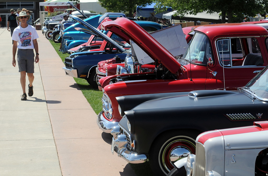 """. Cris Guffey of Fort Collins walks down a row of cars on display at The Ranch in Loveland during the 35th annual Blue Light Special car show put on by the Road Knights Car Club of Loveland. Guffey said his brother is a member of the car club, and he likes to visit the show to spend time with his brother and \""""see what\'s new\"""" among the classic cars. (Photo by Craig Young / Loveland Reporter-Herald)"""