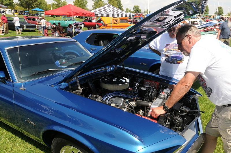 Berthoud resident Bruce Peer, right, looks under the hood of his 1969 Mustang fastback with Dennis Bulera. The Mustang behind Bulera also belongs to Peer and his wife, Angie. He bought both cars while in high school in Southern California. The cars were on display at The Ranch in Loveland during the 35th annual Blue Light Special car show put on by the Road Knights Car Club of Loveland. (Photo by Craig Young / Loveland Reporter-Herald)