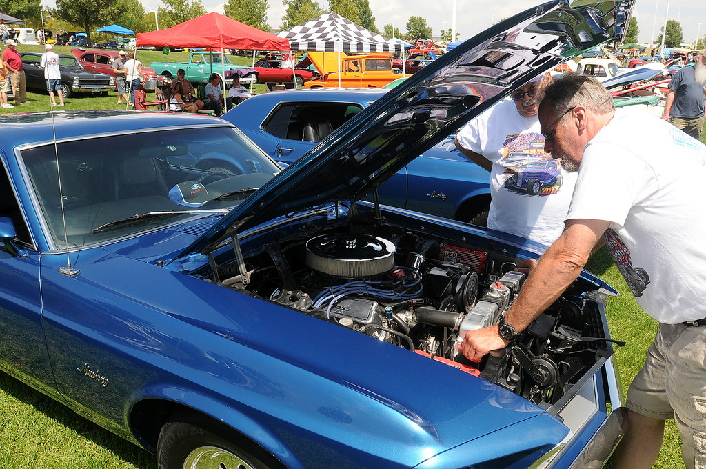 . Berthoud resident Bruce Peer, right, looks under the hood of his 1969 Mustang fastback with Dennis Bulera. The Mustang behind Bulera also belongs to Peer and his wife, Angie. He bought both cars while in high school in Southern California. The cars were on display at The Ranch in Loveland during the 35th annual Blue Light Special car show put on by the Road Knights Car Club of Loveland. (Photo by Craig Young / Loveland Reporter-Herald)