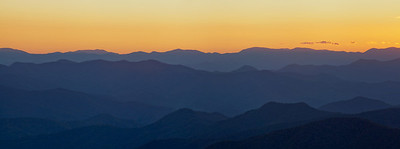 The Blue Ridge Mountains of North Carolina. A popular destination for sunset on the Blue Ridge Parkway is the Cowee Mountains overlook, located on the southern end of the Parkway. The mountains get their name from the bluish color, most noticeably before sunrise and after sunset, from the isoprene released in the air from the trees below.