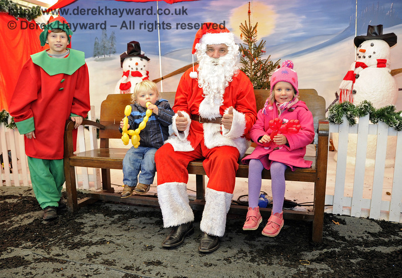 Santa, his Elf, and some happy visitors.  Horsted Keynes 10.12.2011  3203  (I am advised that the two snowmen in the background are not members of the NEP suffering from the effects of the adverse weather).