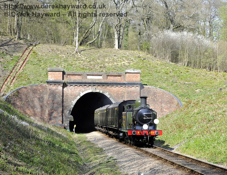 B473 leaves West Hoathly Tunnel with a service train.  The area has recently been extensively improved by the lineside clearance team, and.the work has exposed the two overflows from a stream which runs in a copse above the tunnel (seen on the left of the tunnel).  The stream normally flows into a soakaway over the brow of the hill, but the channels carry any excess water into the railway drainage system if the soakaway overflows.  06.04.2012  4308