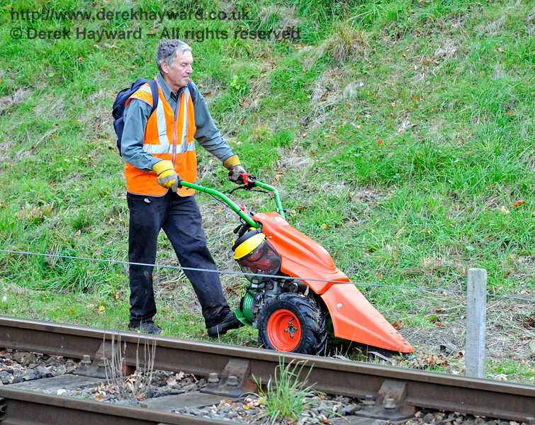 Friends of Kingscote have acquired a new lineside cutting machine which trims a path just over a metre wide, and can cope with quite rough or steep ground.  It is much quicker than either strimming or manual clearing.  The operator is seen here en route back to Kingscote.  10.10.2015  12185