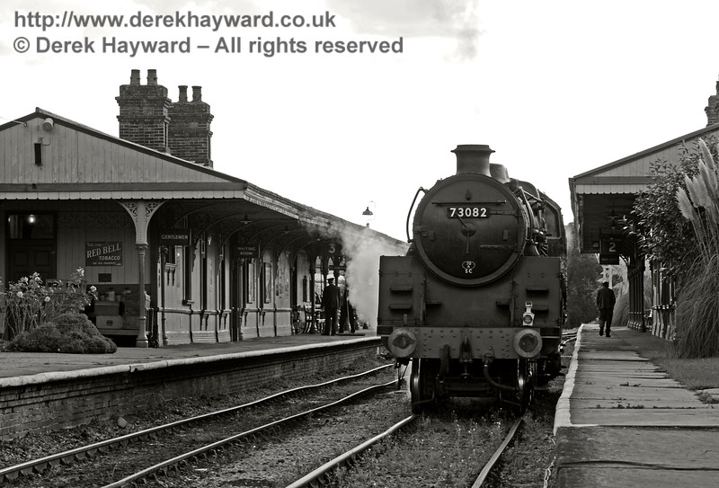 A photo made slightly grainy to reflect the 1950s, with poor quality track, weeds, staff standing about and no passengers.  Once they have renewed the track here it will be impossible to create this effect.  Horsted Keynes 02.10.2016 14151