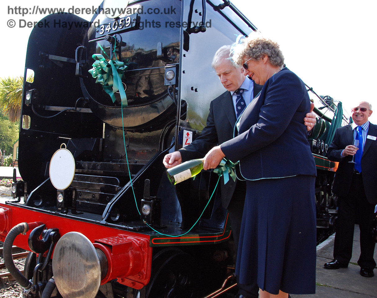 Sally Cruse (assisted by Roy Watts) prepares to break a bottle of champagne on the buffer beam of 34059 Sir Archibald Sinclair as her husband watches in the background. 24.04.2009  0098