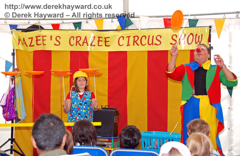 Four plates spinning on the table and two held in the air.  Now for the final trick...!! Hazee's Crazee Circus. Family Fun Weekend Horsted Keynes 29.06.2008