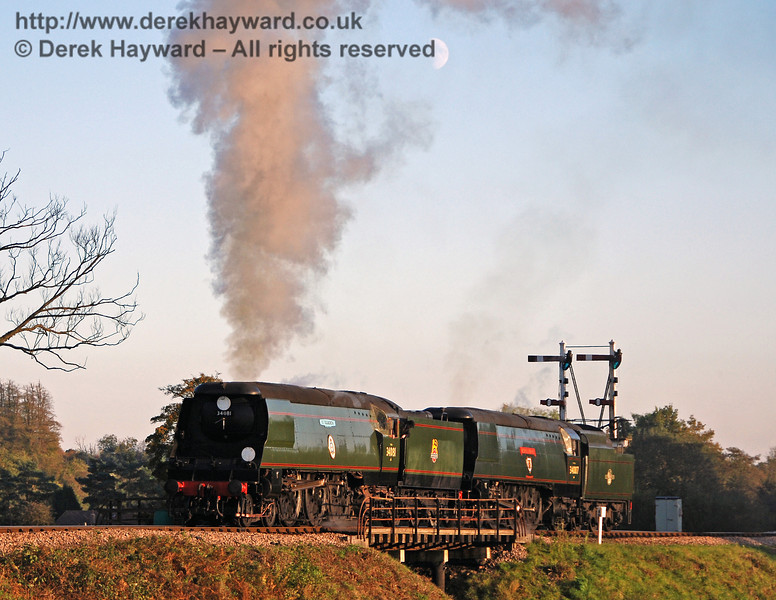 The low winter sun colours the steam, and the moon is in the sky directly above,  as 34081 92 Squadron and 34007 Wadebridge run round at Sheffield Park. 20.10.2007