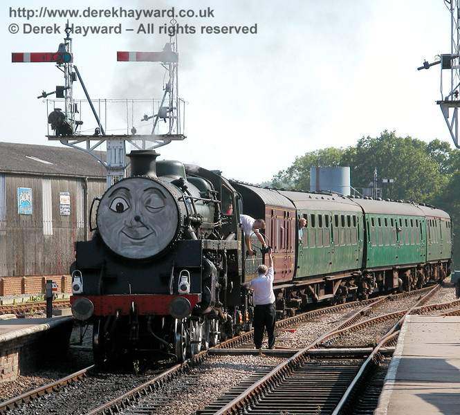 75027 winks at the camera while the signalman exchanges tokens with the fireman.  Horsted Keynes 24.06.2006