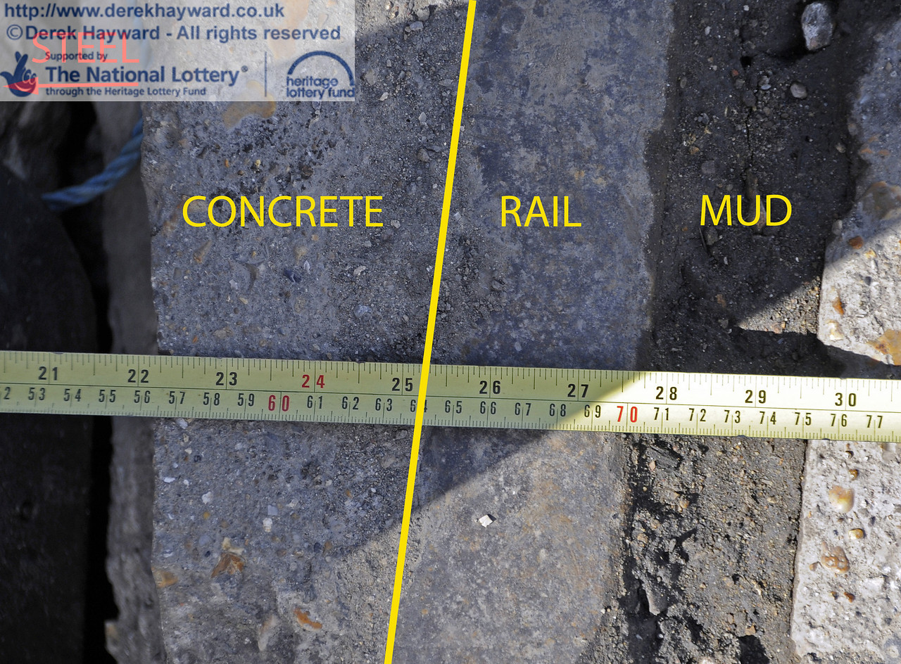 A close up of the area of restricted clearance.  The steel upright is to the left.  The boundary between the outer (western) edge of the rail is difficult to see, and has been denoted by the yellow line.  Mud currently fills the flange gap, and will, no doubt, be cleared as judged necessary after the building work.  There is just over 25 inches (64cms) of clearance from the outer edge of the rail (the outer edge of a wheel on a locomotive).  In a statement the railway has said this is satisfactory for the tramway, where movements are very slow and controlled.  15.04.2012  4438