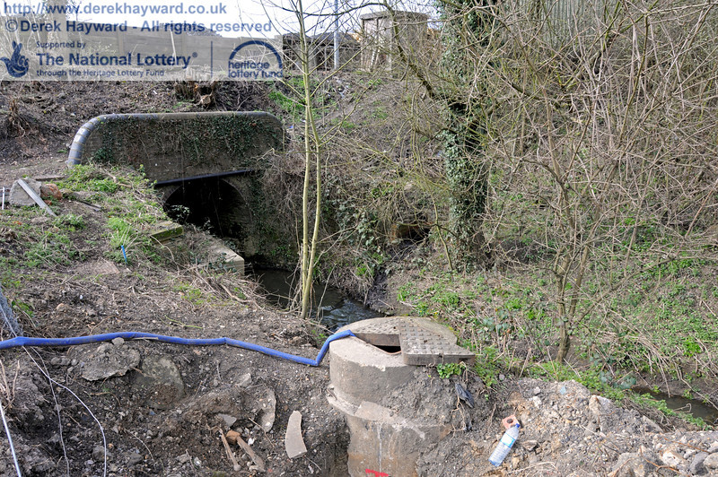A tributary to the River Ouse flows east under the railway through a culvert adjacent to the car park, and the sewer also passes under the railway in a separate pipe at this point.  The manhole to access the sewer is open as work takes place to connect new pipes.  09.03.2011  6154