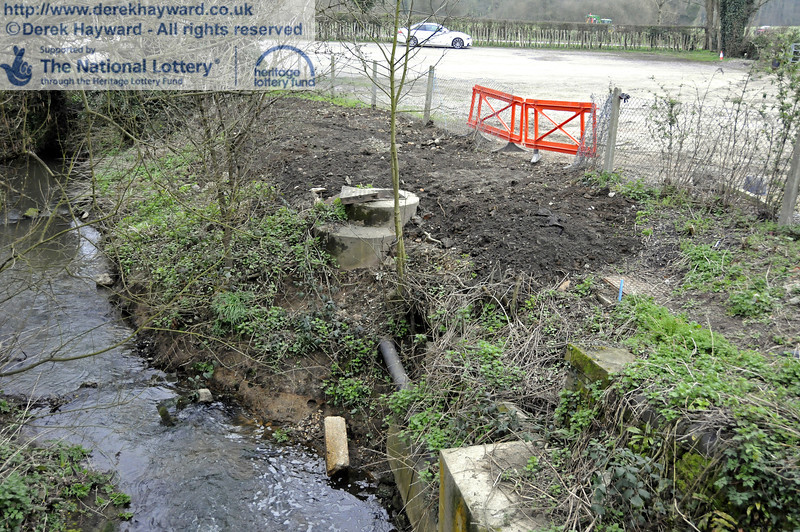 New drains have been connected to the existing sewer pipe via the concrete inspection chamber in the centre of the picture.  This view looks east with a tributary to the River Ouse emerging from a culvert under the railway behind the camera.  The sewer also crosses the railway at this point and the river embankment has broken away and exposed a short length of the main pipe at the bottom of the picture.  Nearer to the camera the sewer pipe is encased in a large concrete block as it enters the culvert to pass under the railway.  To the right of the inspection chamber the ground has been made good, but the fence has yet to be replaced.  17.03.2011  6512