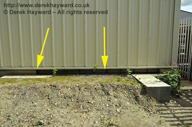 The northern end of the base of the Carriage Shed, showing the modifications made to allow the possible future extension of A road out of the northern end of the shed.  The left hand arrow indicates the end of the solid concrete base (which would obstruct track) and the right hand arrow shows the gap for track which has been filled by blockwork (capable of removal).  Elsewhere in this gallery pictures show that the cladding allows the future provision of a roller shutter above.  24.07.2011  2386