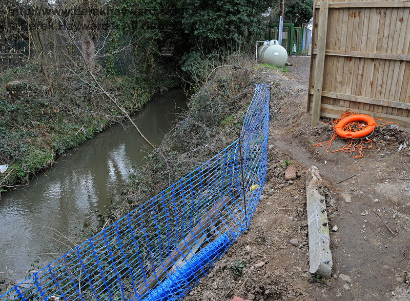 A river runs adjacent to the site of the new water tank.  A safety fence and lifebelt were in situ during the works.  09.03.2011  6125