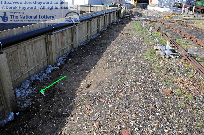 Although mainly hidden by earth a low gabion wall has been added adjacent to the boundary fence. The cage can just be seen near the green arrow.  This is assumed to improve stability and drainage near the fence. 24.02.2011  5995