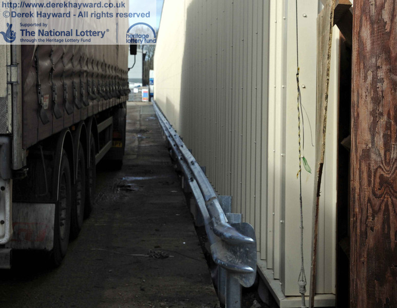A dreadful picture of the side of a lorry, but it shows that the new concrete strip has been laid on the western site boundary, and a crash barrier protects the side of the carriage shed. 24.02.2011  5930