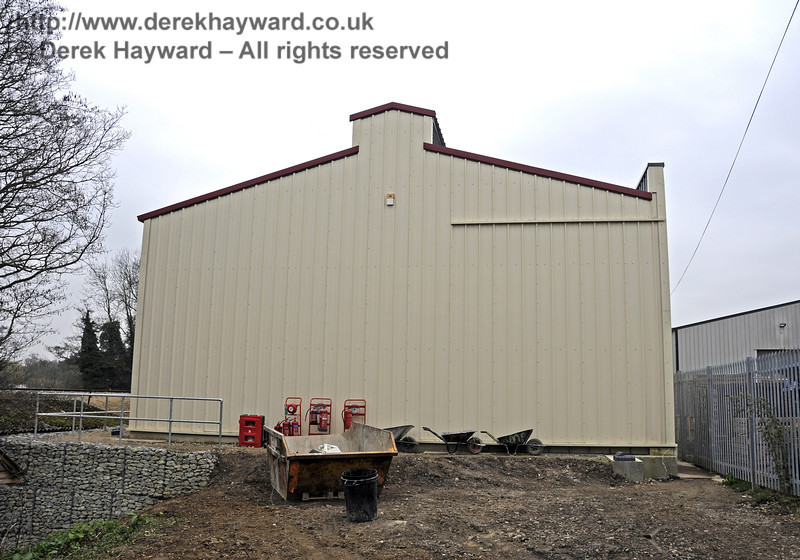 Looking south at the rear of the Carriage Shed along a strip of land owned by the railway.  It would, in theory, be possible to extend A road of the shed north through the shed wall to create a siding here and provision has been made for a subsequent installation of a roller shutter in the north wall.  A small ridge in the cladding can be seen on the right of the shed where a door could be inserted. At present no financial provision exists for this extension.  17.03.2011  6453
