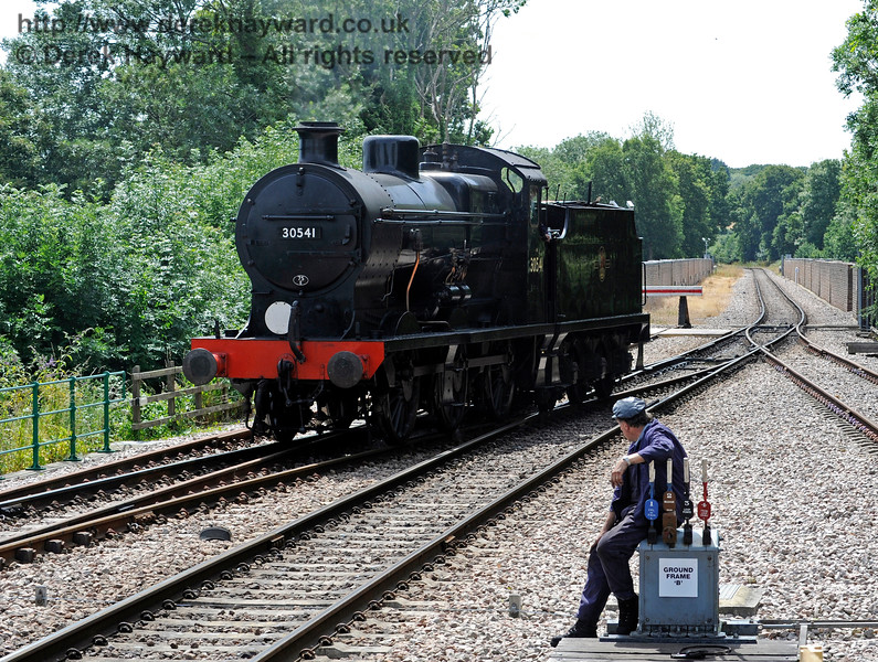 A member of the crew sits and watches as 30541 runs round at East Grinstead.  18.07.2015  11657