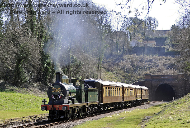 592 passes through the site of West Hoathly station with the Golden Arrow.  16.03.2014  8719