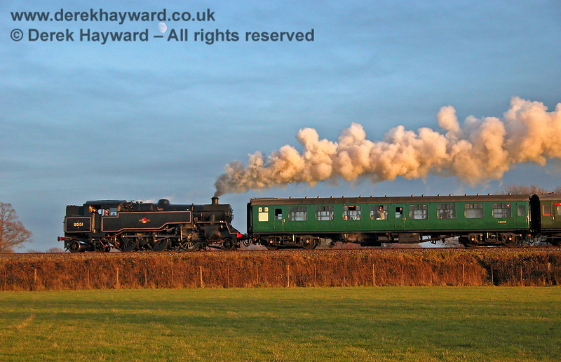 It's December and the setting sun produces a rich golden glow as it sinks below the horizon.  As the light fades 80151 steams north into Horsted Keynes, with the moon in the sky above. 11.12.2005